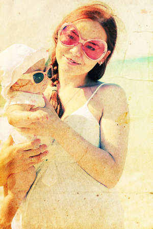 Portrait of happy loving mother and her baby at the beach photo