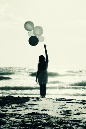 beautiful woman with colorful balloons on seaside  photo