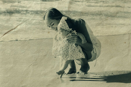 portrait of young mother and her cute baby on the seaside photo