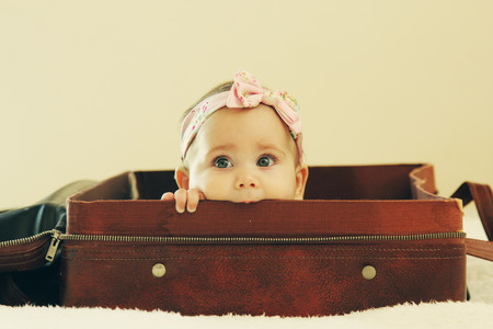 Portrait of aborable baby lying in vintage bag photo