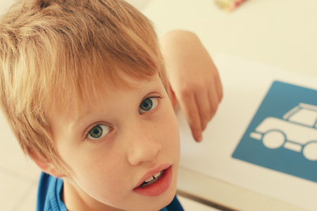 cute 6 years old boy drawing  photo