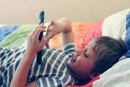 Cute boy using a mobile phone photo