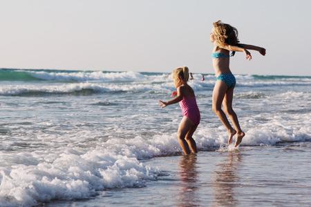 サンセット ビーチで遊んで二つの幸せな子供