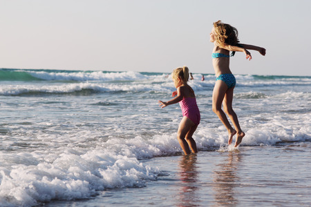 two happy kids playing on the beach at sunset