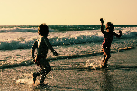 two happy kids playing on the beach at sunset photo