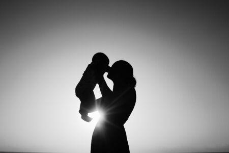 silueta niño: Silueta de la madre y el bebé al atardecer