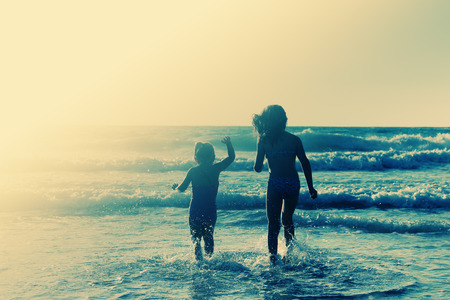 active holiday: two happy kids playing on the beach at sunset