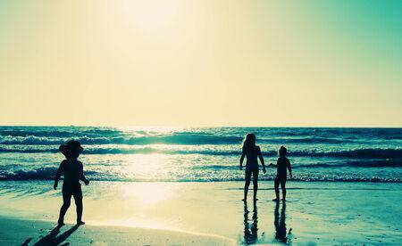 kids on the beach at sunset photo