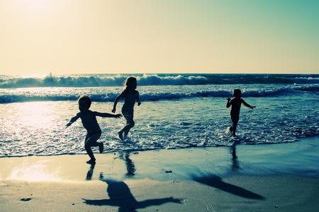 ni�os caminando: ni�os felices jugando en la playa al atardecer