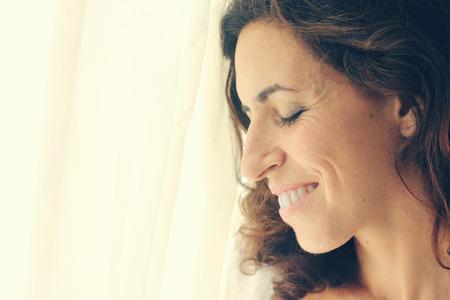 ojos marrones: hermosa mujer de 35 a�os de edad, se encuentra cerca de la ventana Foto de archivo