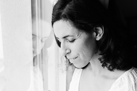 beautiful 35 year old woman stands near the window photo