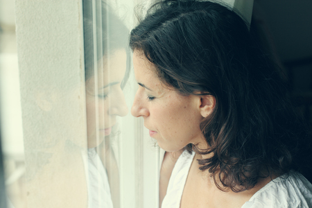 beautiful mother and daughter standing near the window photo