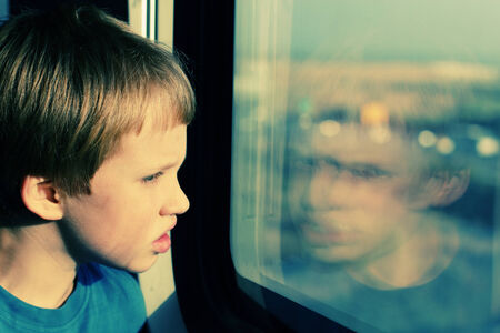 Boy looking through the window photo