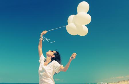 woman with white balloons on seaside Foto de archivo