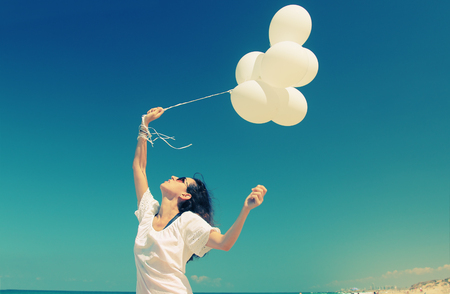 summer vacation: woman with white balloons on seaside Stock Photo