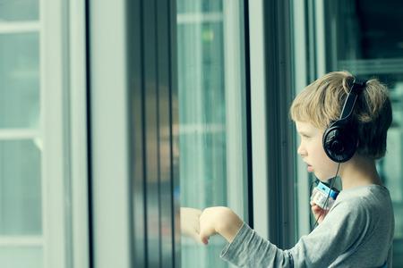 空港で窓の外見ているヘッドフォンを持つ少年