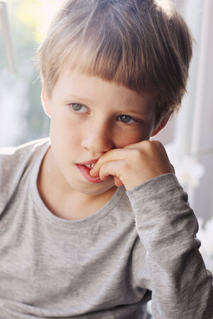 Cute 6 years old boy sitting near the window photo