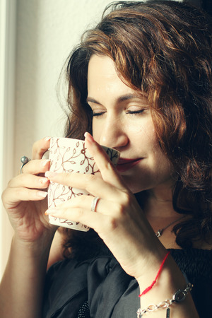 35 years old: beautiful 35 years old woman holding cup of morning coffee