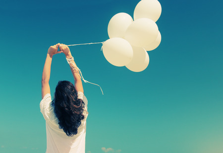 freedom woman: woman with white balloons on seaside Stock Photo