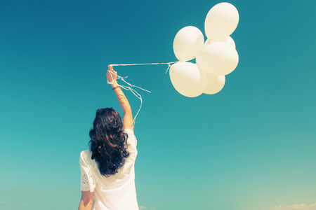 woman with white balloons on seaside Stock Photo
