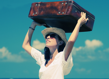 woman with suitcase on the beach photo