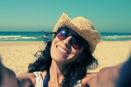 Beautiful girl smiling on the beach with the sand, sea and blue sky in the background. Selfie. photo