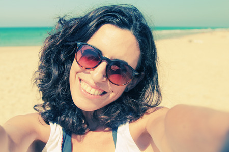 blissful: Beautiful girl smiling on the beach with the sand, sea and blue sky in the background. Selfie.