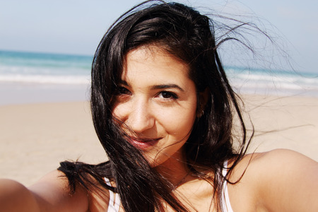 Beautiful girl smiling on the beach with the sand, sea and blue sky in the background. Selfie.