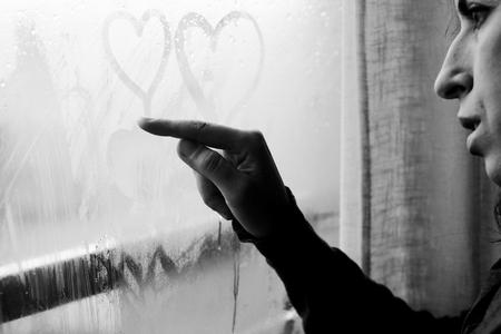 woman drawing heart on wet window photo