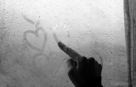 woman drawing heart on wet window.   photo