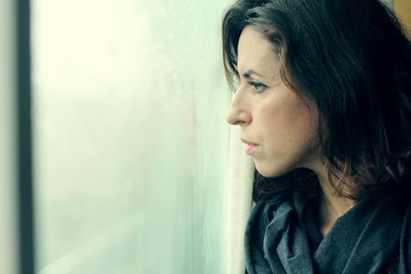 아름다운 35 세 여성이 창문 앞에 선다. 스톡 콘텐츠