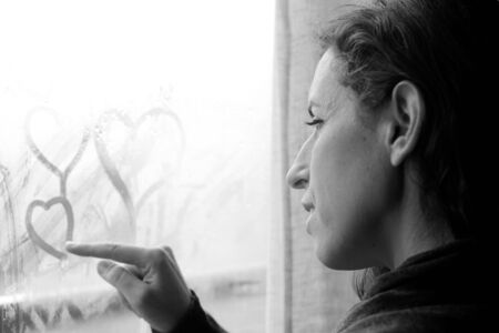 mid adult woman looking out of the window photo
