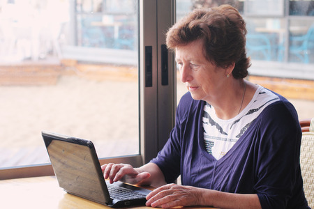 senior woman sitting on the cafe with laptop photo