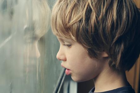 かわいい 6 歳の少年は窓を見る