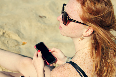 young woman holding smartphone photo