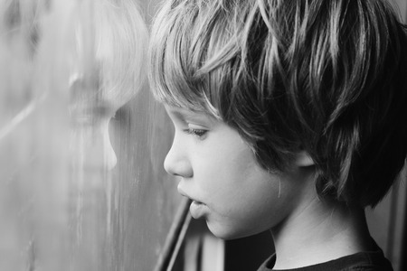 Cute 6 years old boy looking through the window Banque d'images