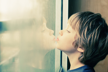 boy long hair: Cute 6 years old boy looking through the window Stock Photo
