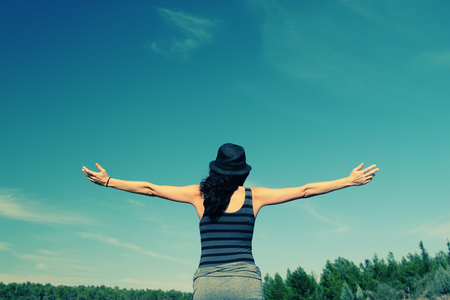 young woman looking up with open arms over sky background