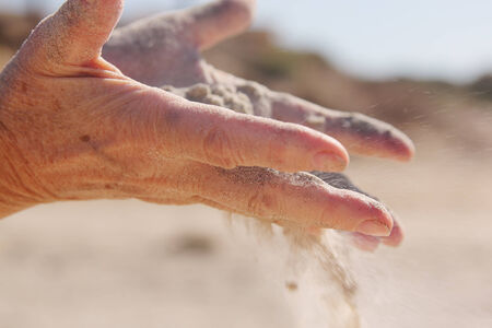 trickle down: woman with sand in hands