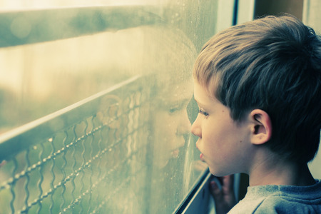 6 years: Cute 6 years old boy looking through the window Stock Photo
