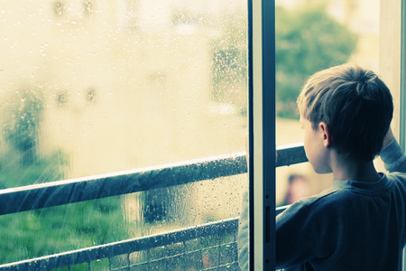 Cute 6 years old boy looking at the rain photo