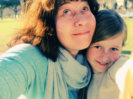 8 year old girl: Funny selfie portrait mother and daughter outdoors Stock Photo