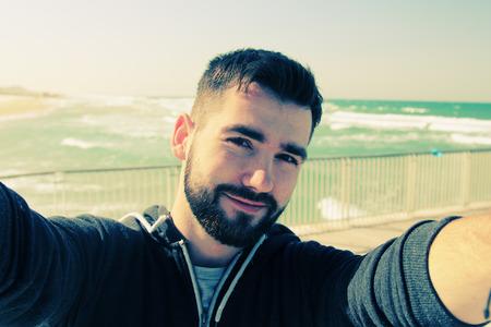 cabello: retrato Autofoto del hombre joven al aire libre Foto de archivo