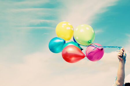 colorful sky: Man holding colorful balloons outside Stock Photo