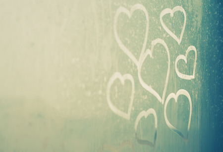 drawing hearts on wet window photo