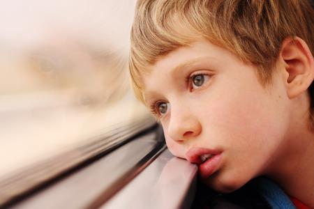 bambini pensierosi: Ragazzo sveglio guardando attraverso la finestra Archivio Fotografico
