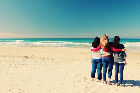 海辺で歩いている 3 人の親友