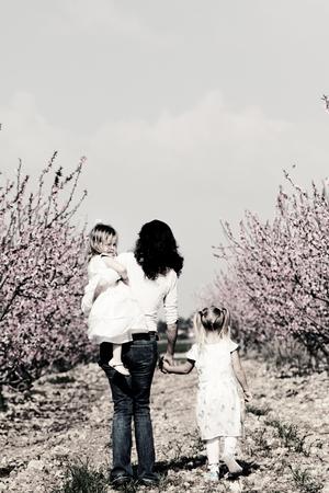 niños caminando: madre e hijas caminando juntos en el parque