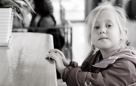 Adorable 4 years old girl sitting in cafe photo