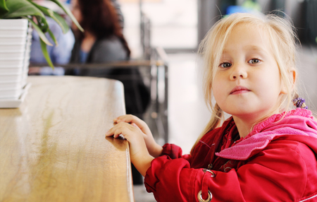 4 years old: Adorable 4 years old girl sitting in cafe Stock Photo
